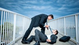 Caucasian businessmen fighting on elevated walkway