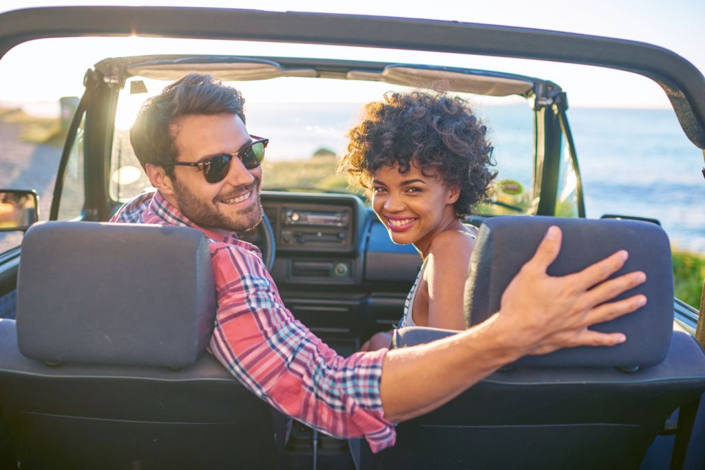 Young couple sitting in their car during roadtrip
