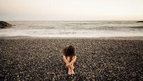 Young sad woman alone in a black stone beach.