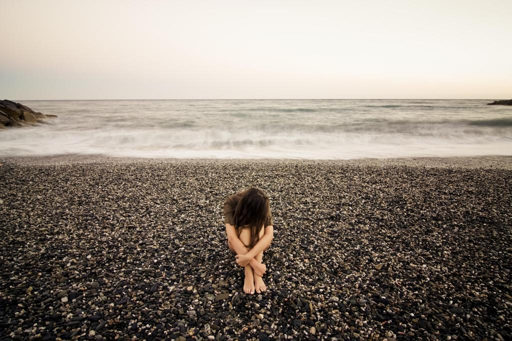 Young sad woman alone in a black stone beach.