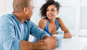 African American couple drinking coffee and communicating in kitchen.