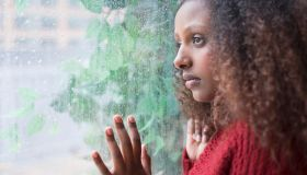 Black woman looking out rainy window