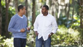 Young man talking with father in park