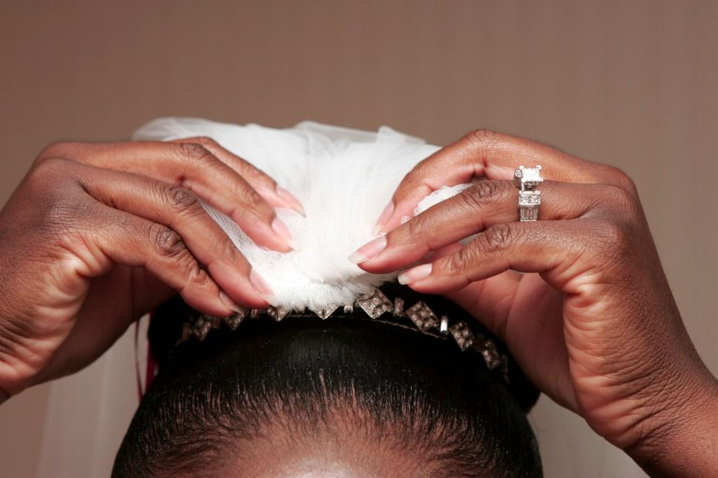 Detail of African-American bride putting on her tiara