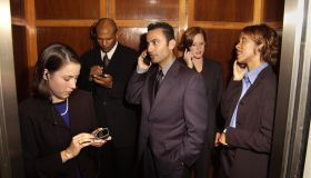 Businesspeople using cellular phones in elevator