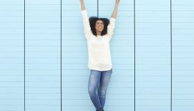 Full length portrait of a cheerful young woman smiling with hands in the air
