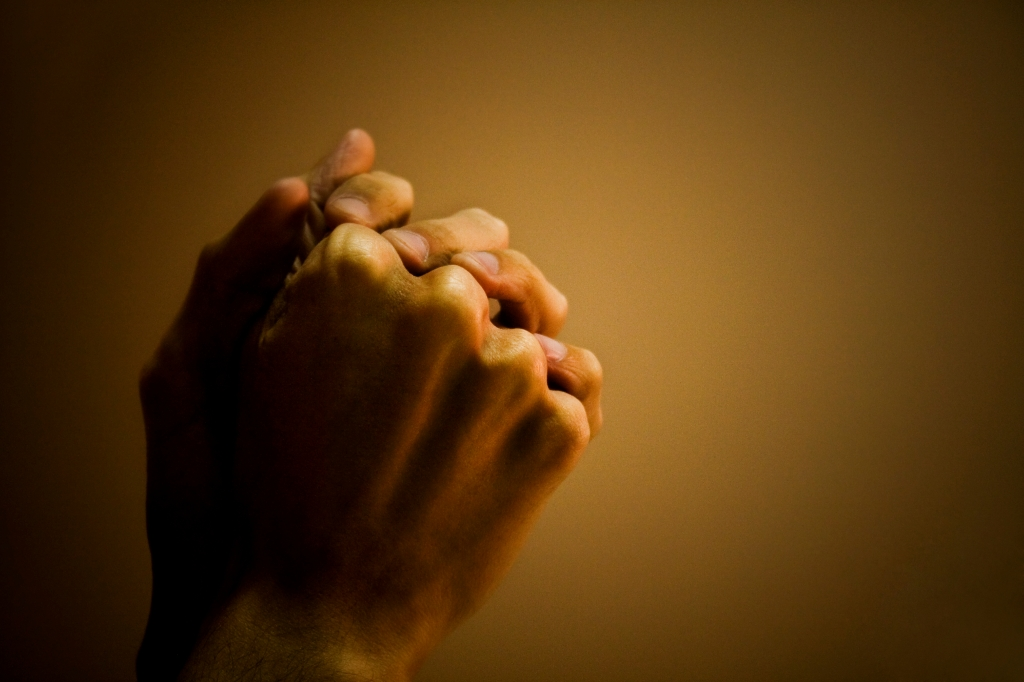 Close-up of a man's hand praying