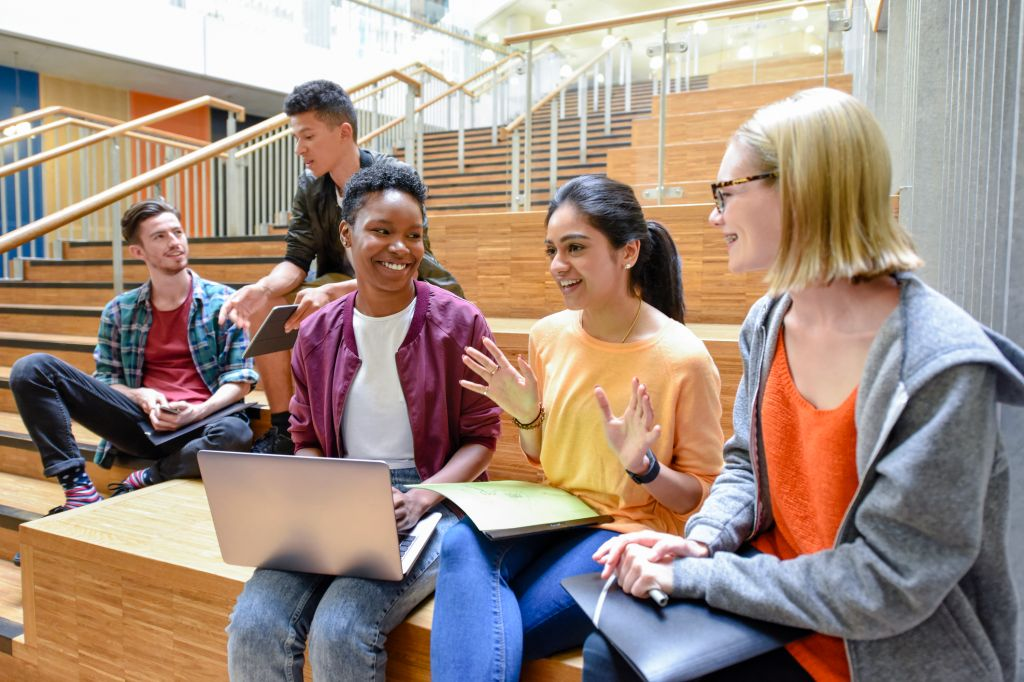 Cheerful female college friends sitting on steps with laptop and folders