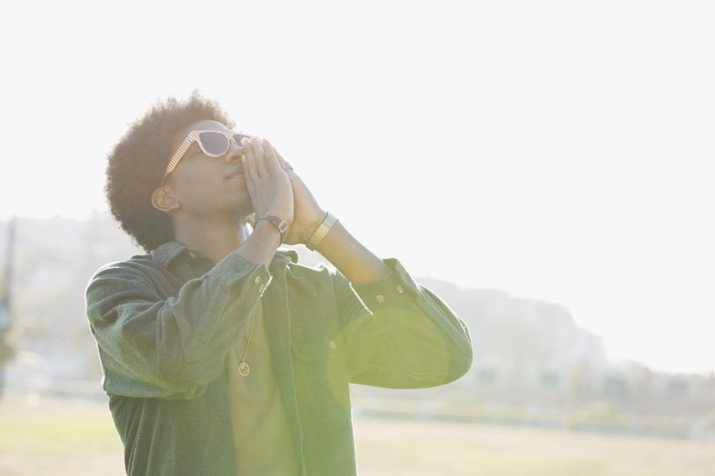Man standing outdoors praying