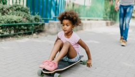 Girl playing with skateboard outdoors