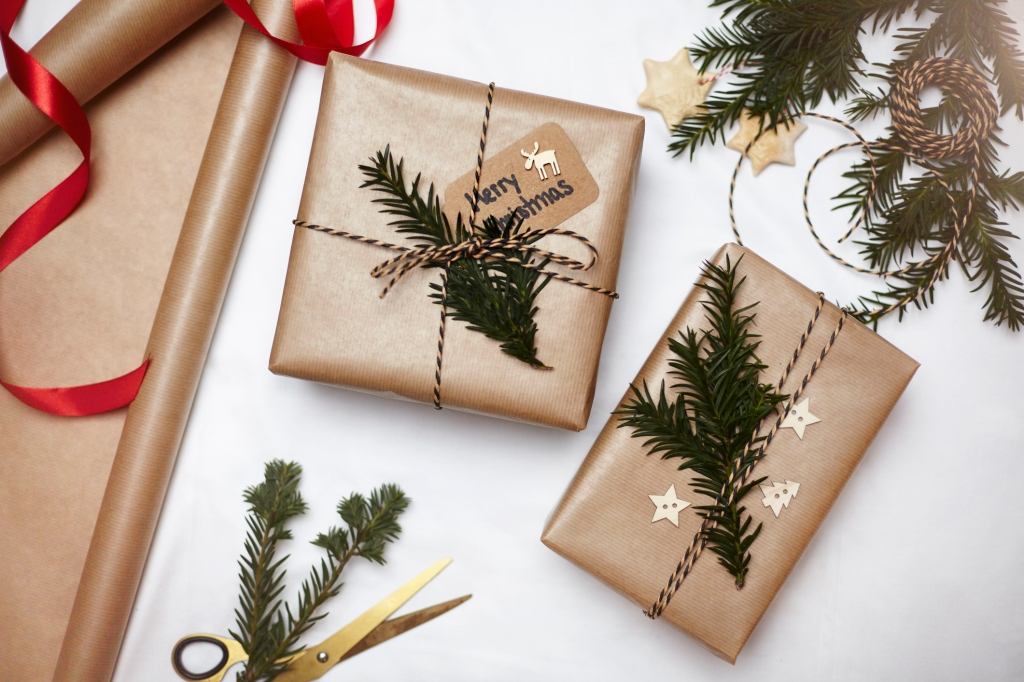 Christmas gifts wrapped in brown paper, decorated with fern and string, overhead view