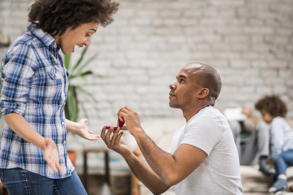 Young black man proposing to his girlfriend in the living room.