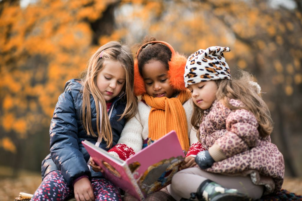 Three small girls reading a children's book in autumn day.