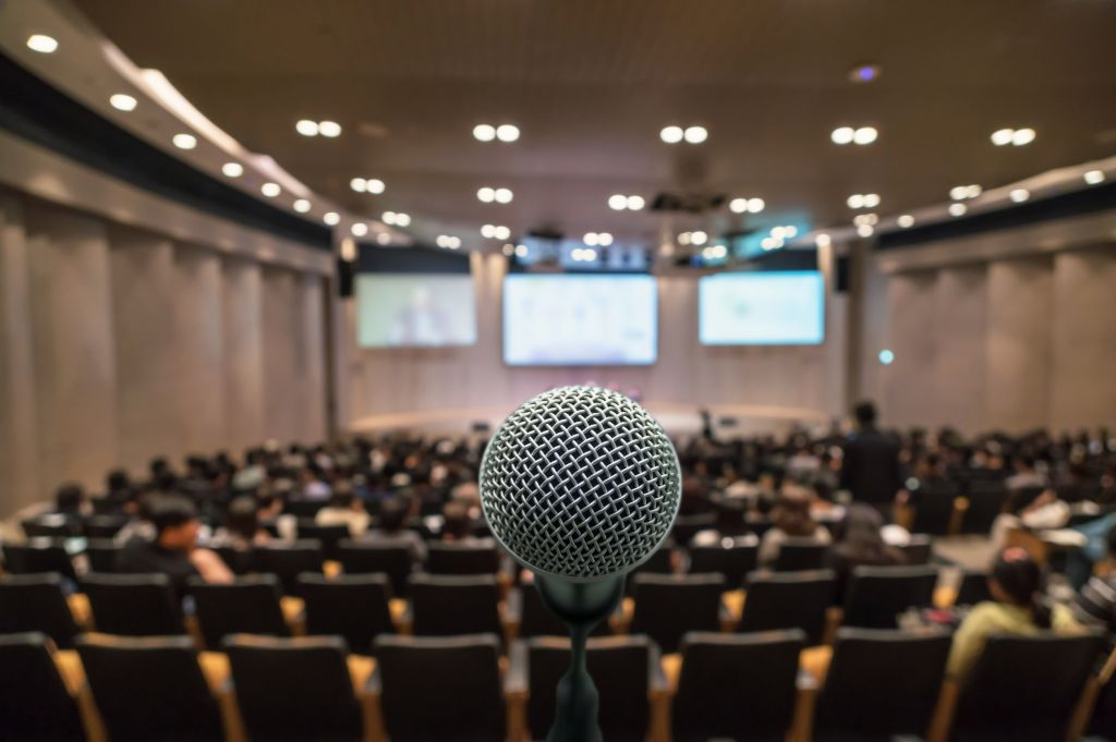 Business meeting concept, Microphone over the Abstract blurred photo of conference hall background