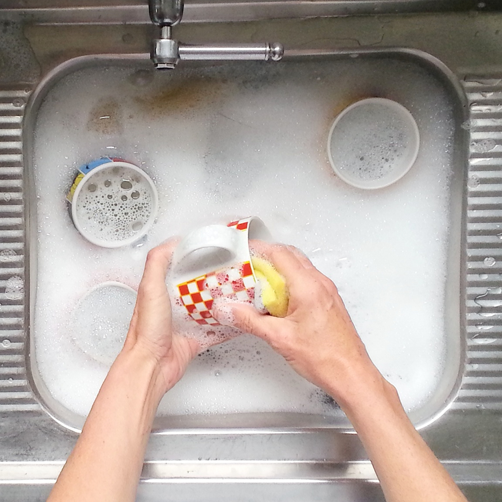 Cropped Image Of Hands Washing Cups In Sink