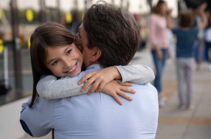 Daughter hugging her father at the airport