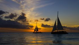 Silhouette of Two Sailboats on Ocean at Sunset