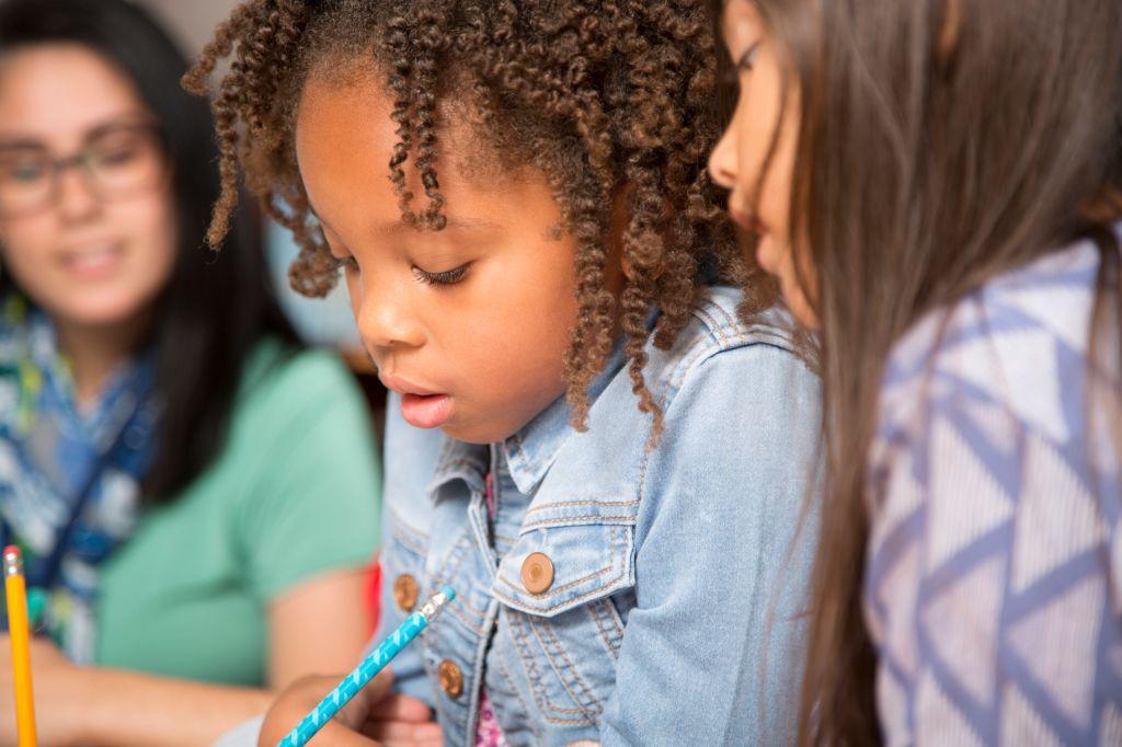 Teacher, mentor helps elementary-age schoolgirls with homework.