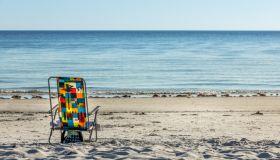 Deck Chair On Beach Against Clear Sky