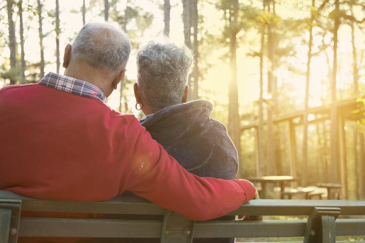Active senior adult couple enjoy outdoor park at sunset.