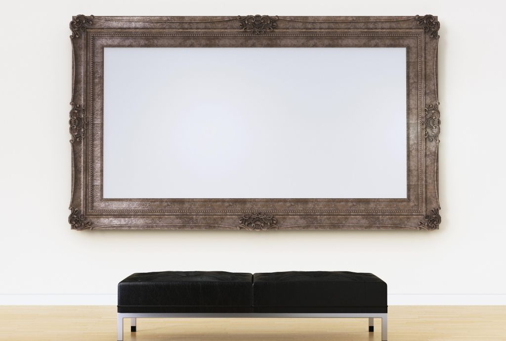 Empty picture frame above bench in art gallery