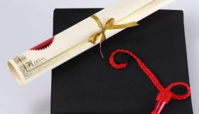 High Angle View Of Mortarboard And Diploma On White Background