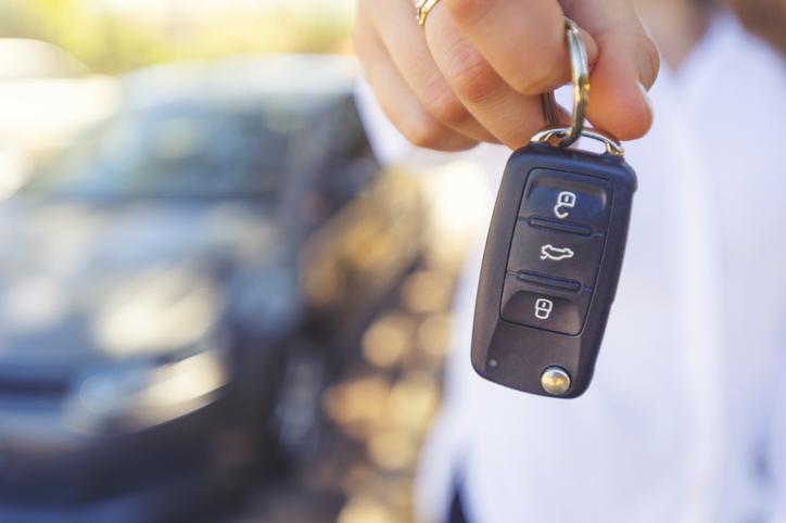 Female car salesperson handing over the new car keys