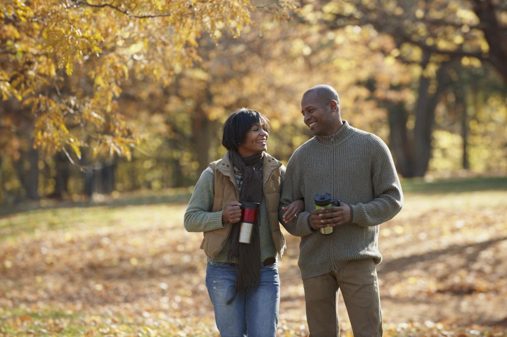 Black couple walking together in park in autumn