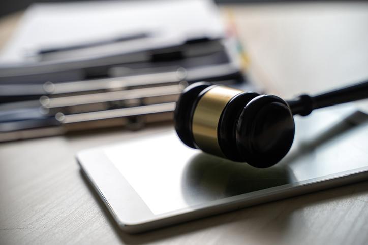 Close-Up Of Gavel On Digital Tablet At Desk