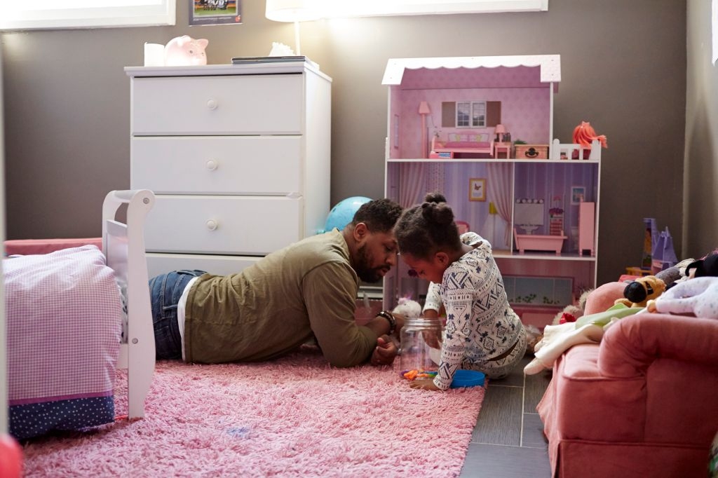 Father and daughter playing by her dolls house