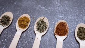 spices in wooden spoons on a gray background. cooking, a place to copy