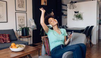 Beautiful Afro woman enjoying her favorite music at home