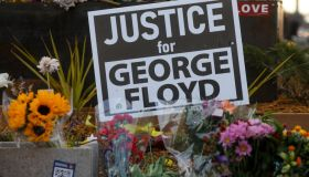 People lay flowers at a memorial in George Floyd Square...