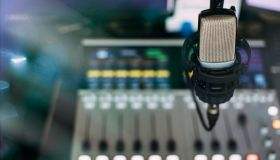 Radio broadcast studio with microphone and sound mixer console on the background