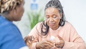 Elderly woman discussing treatment with nurse